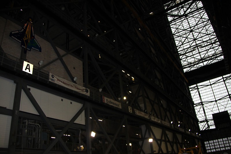 Banners signed by the teams that supported each Space Shuttle mission hang in the Vehicle Assembly Building.  In the upper left of the photo is the mission patch for STS-107, which ended with the loss of Columbia and her crew.  Behind the cinderblock wall is the final resting place of the debris recovered from the accident.