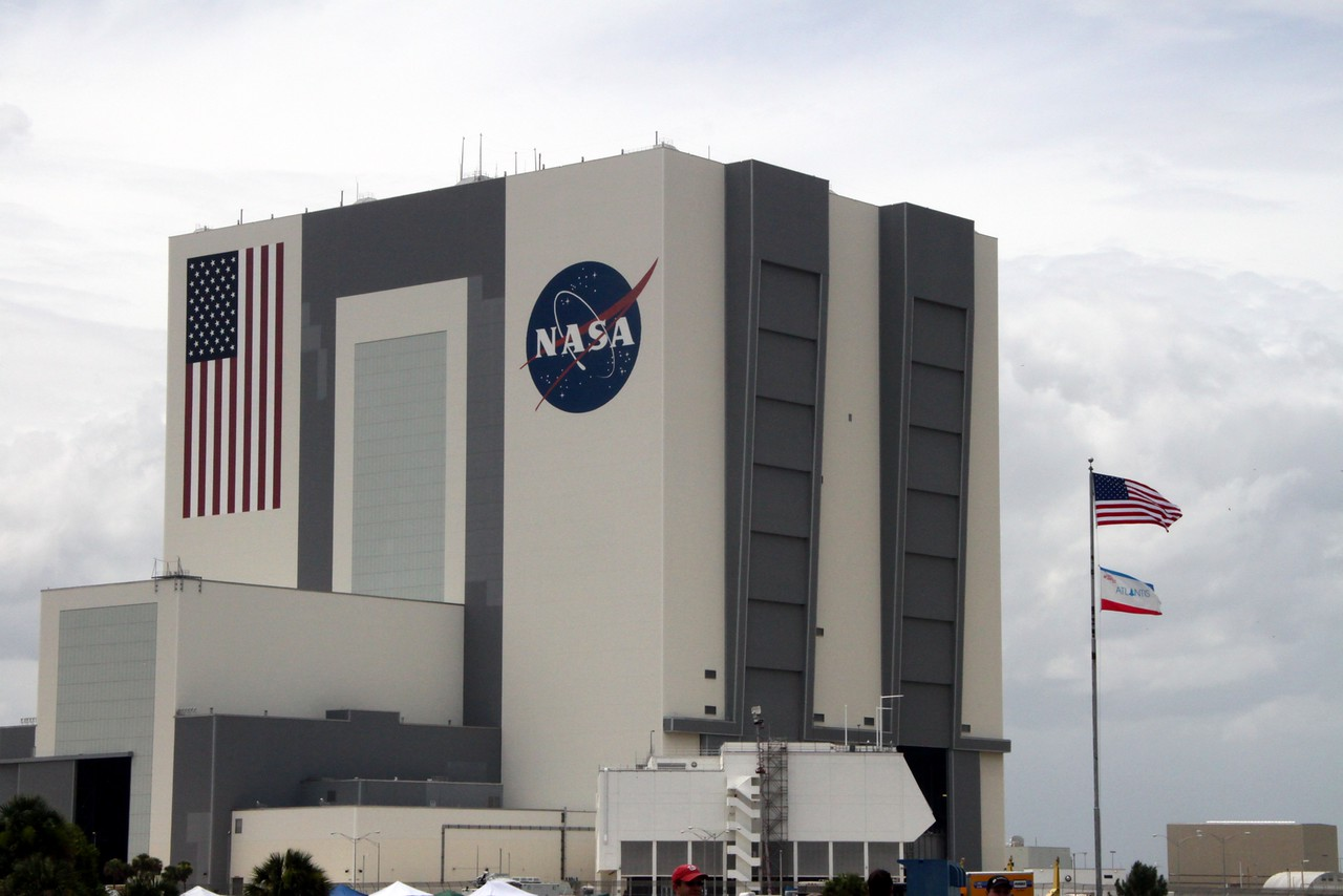 The Vehicle Assembly Building on launch day, with the flags of the United States and Atlantis flying.  The white structure in the foreground is the end of the Launch Control Center (LCC).