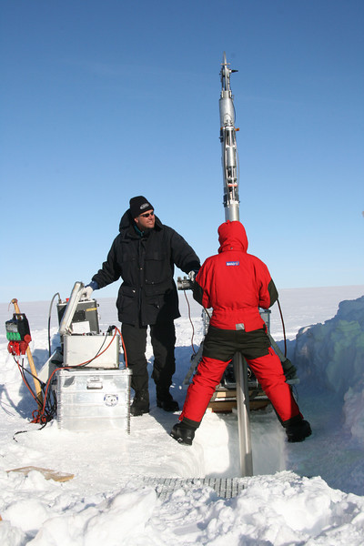 The ice core drill is lowered into the bore hole.