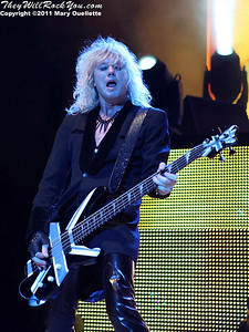 """Rick Savage of Def Leppard performs on June 30, 2011 during the """"Mirrorball Tour"""" at the Comcast Center in Mansfield, Massachusetts."""