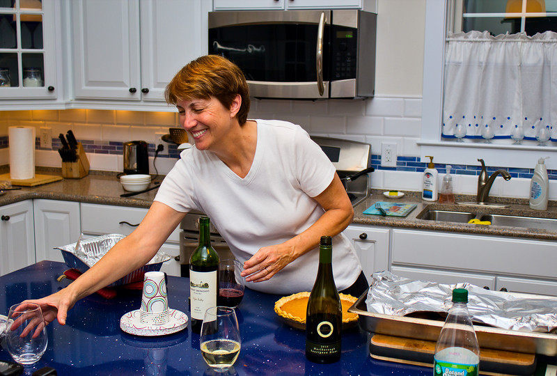 With one glass of wine in front of her, Celeste reaches for another.  Cooking Thanksgiving dinner can be trying.