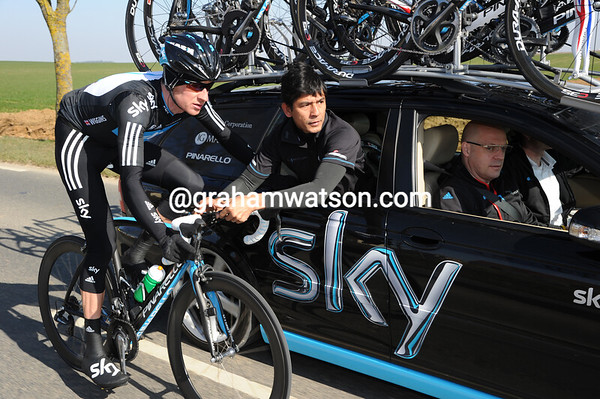 Bradley Wiggins is getting his bars tightened by a Sky mechanic...