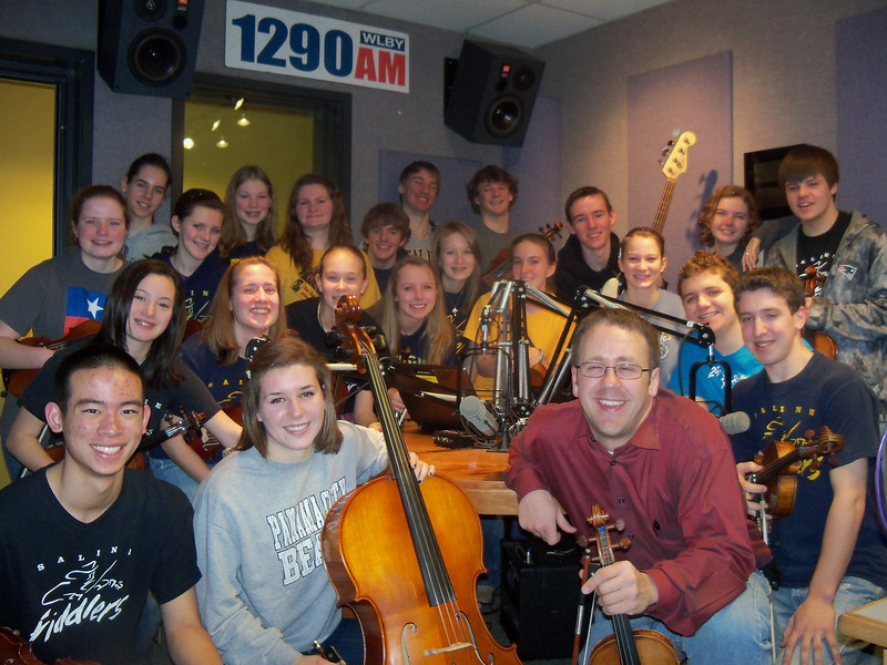 """Saline Fiddlers live on air with WLBY 1290AM Lucy Ann Lance radio show. Saline Fiddlers were promoting their February 12th, 2011 Hometown show that will feature guest artist The Ragbirds. Fiddlers played some tunes for the radio audience and answered questions about all the activities and going on's in the busy Saline Fiddler schedule. A big surprise was brought to them by show host Lucy Ann Lance when she told them about some of the fun things they will be doing and places they will perform on their upcoming summer tour thru Wisconsin and northern Michigan this year. Lucy got the insider information from the Booking Manager of the group and excited them! Hear the podcast of the show here <a href=""""http://lucyannlance.com/"""">http://lucyannlance.com/</a> Photos courtesy Lucy Ann Lance"""