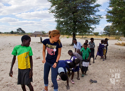TASIS student leads games at a Zambian school.