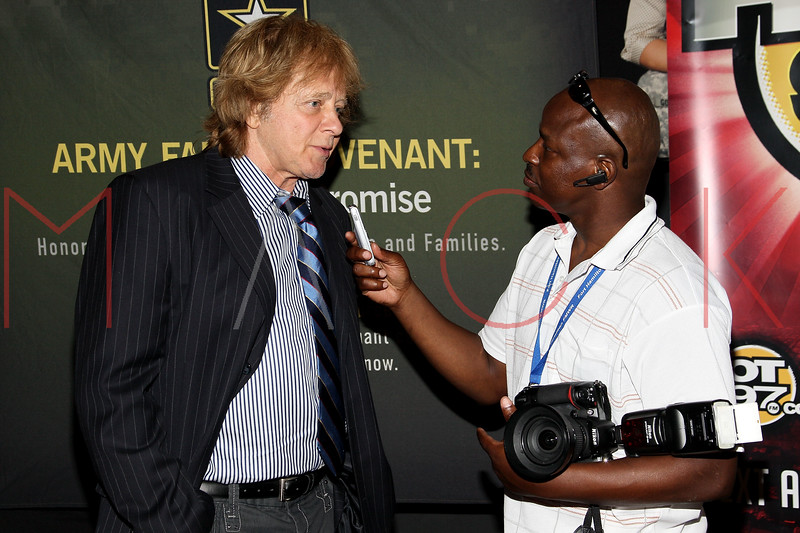 NEW YORK, NY - JULY 01:  Eddie Money (L) being interviewed by Fort Hamilton military base spokesperson Bruce Hill during a free Independence Day concert and fireworks display at 101st Street and Ft. Hamilton Parkway on July 1, 2012 in the Brooklyn borough of New York City.  (Photo by Steve Mack/S.D. Mack Pictures)