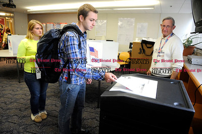 11/1/2012 Mike Orazzi | Staff Bristol Central High School students Skylar Wright and David Ryskowski place their ballots into the electronic counter as volunteer Wayne Fuller looks on during a mock election on Thursday at Central.