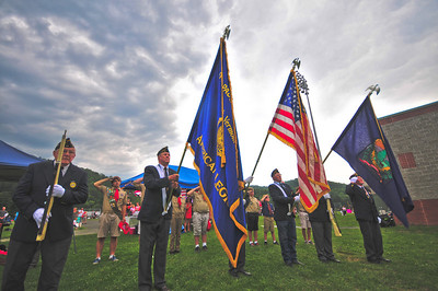 Members of the American Legion and several Scouts salute the flag