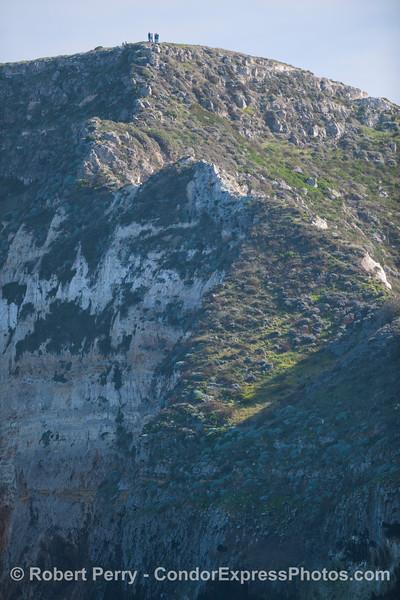 Hikers on cliff north face of Santa Cruz Island.