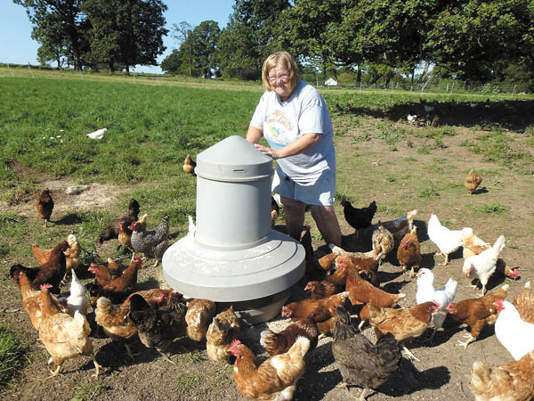 Debbie Wachter/NEWS<br /> Maggie Henry shakes naturally grown grain and seed for her chickens that are raised on her certified organic farm.