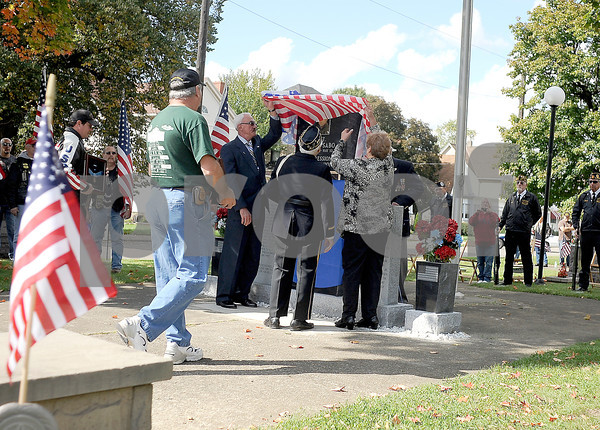 Courtney Caughey-Stambul/NEWS<br /> George Sabo, left, and Rosemary Sabo-Brown, right, with the help of Samuel Teolis, center, unveil the monument dedicated to Specialist Four Leslie H. Sabo, Jr.