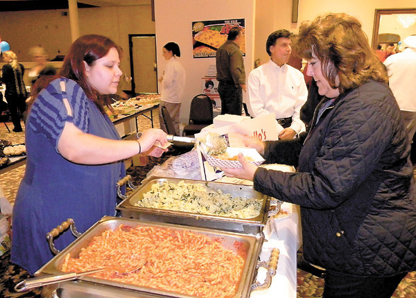 Dan Irwin/NEWS<br /> Alisha Haney serves some pasta from Gallo's Italian Villa to Kim Thompson of New Castle at last night's Taste of the Town. At rear is restaurant owner Phil Gallo.