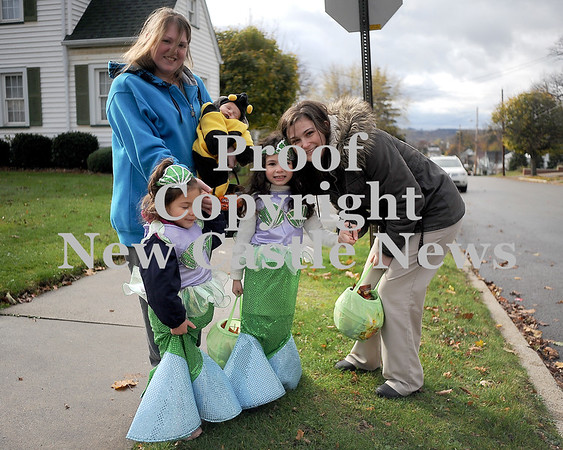 Courtney Caughey-Stambul/NEWS<br /> A family of trick-or-treaters stops for a photo while collecting candy in New Castle on Saturday.