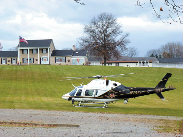 Debbie Wachter/NEWS<br /> A state police helicopter flies in from Franklin, ready to assist state troopers if needed for a Marcellus Shale drilling protest on Route 551 in North Beaver Township. The landing base was next to Westfield Presbyterian Church.