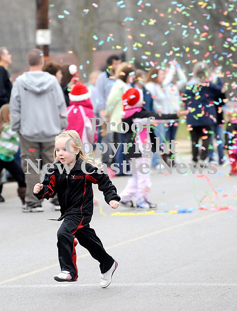Courtney Caughey-Stambul/NEWS<br /> Lina Coffman, 4, runs across Main Street to secure her spot to watch the annual Wampum Christmas parade on Saturday.