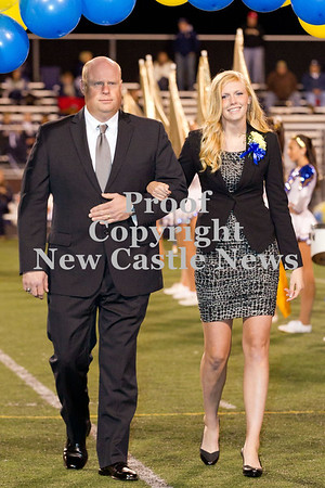 Scott R. Galvin / NEWS<br /> Wilmington Area High School homecoming court member Anna Miller is escorted by her father Don during halftime of the football game on Friday.