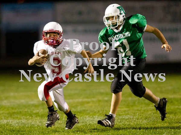 Scott R. Galvin / NEWS<br /> Neshannock quarterback Jared Staph (9)eludes the pursuit of Riverside defender Chase Altman in the fourth quarter of the junior high football championship match at Riverside on Thursday.  RIverside won 59-6 and went undefeated for the season.