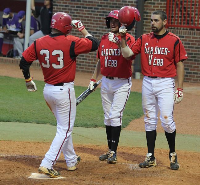 Teammates congradulate Brad Collins, 33, for a homerun.