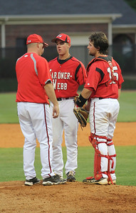 Andrew Barnett and Dusty Quattlebaum meet with a coach on the mound.