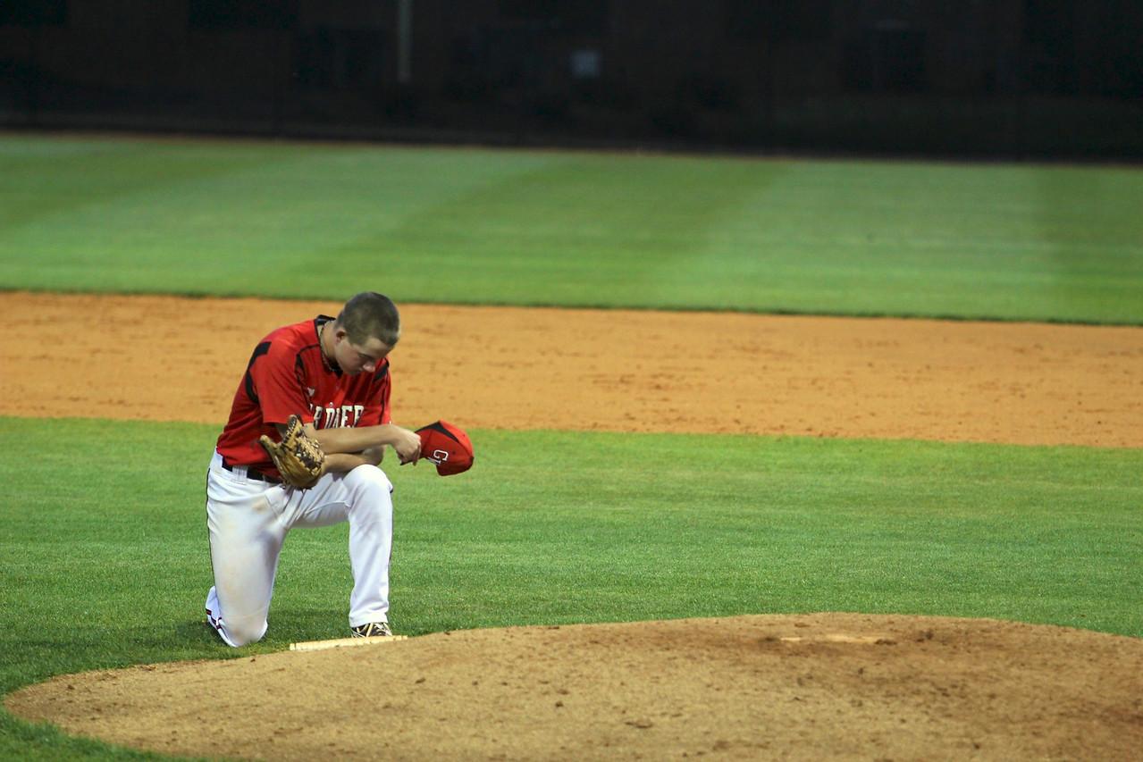Number 10, Andrew Barnett, kneels at the mound before the start of the inning.