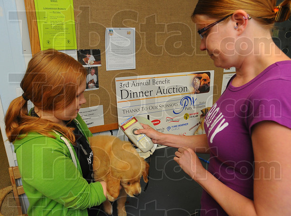 """Tribune-Star/Jim Avelis<br /> Checks out: Luann Baer holds """"Poppy"""" while Kali Skinner checks the performance of the ID chip they just inserted under the puppy's skin."""