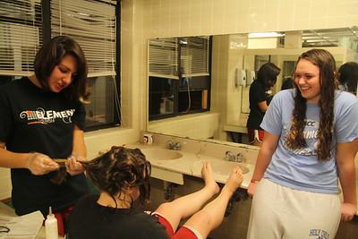 Melanie Mikus watches as Caroline Nethery dyes Julia Kiser's hair in Decker's bathroom.