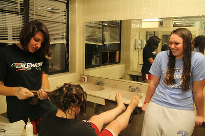 Melanie Mikus watches as Caroline Nethery dyes Julia Kiser's hair in Decker's bathroom.