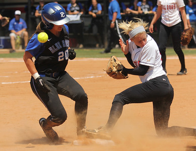 Jordyn Arrowood, 13, gets the ball knocked out of her hand as the opposing player slides into third base.