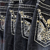 Tribune-Star/Jim Avelis<br /> Eye catchers: Sparkles adorn the back pockets of jeans for sale at Lynn's Boutique, located in the old Book Nation in downtown Terre Haute.