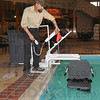 Tribune-Star/Jim Avelis<br /> Quick set up: Terre Haute Holiday Inn chief engineer Brian Rice demonstrates the deployment of the portable chair lift at the pool in Terre Haute Friday afternoon. The device is highly portable and can be set up in minutes.