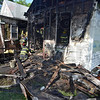 Tribune-Star/Jim Avelis<br /> Gutted: Terre Haute city firefighters mop up after a fire on south 12th street that damaged two homes Thursday evening. The late afternoon fire severely damaged the home on the right and caused external damage to its neighbor.