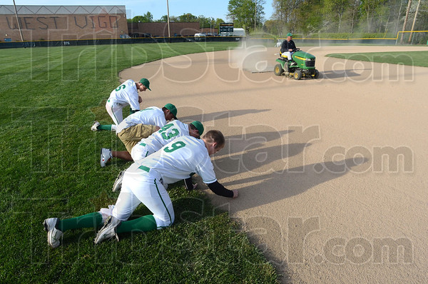 Tribune-Star/Jim Avelis<br /> Weed free: West Vigo baseball team members Duston Bryan, Kyle Stewart, Brody Donnelly and Austin Wallace pull weeds from the edge of the outfield after a game last week.