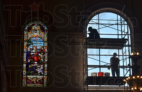 Tribune-Star/Joseph C. Garza<br /> After and before: Alfredo Reyna, top, and Leroy Thornburg, bottom, of Bovard Studio, Inc., are silhouetted as they prepare a window for stain glass panels after they finished the window on the left at the Church of the Immaculate Conception at St. Mary-of-the-Woods Wednesday.