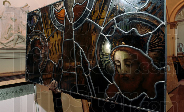 Tribune-Star/Joseph C. Garza<br /> Art of Heaven: Alfredo Reyna of Bovard Studio, Inc., lifts a piece of stained glass out of a container as he and his co-workers place the pieces into frames at the Church of the Immaculate Conception Wednesday at St. Mary-of-the-Woods.