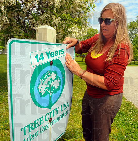 """Tribune-Star/Jim Avelis<br /> On a roll: Terre Haute urban forester Sheryle Dell places a sticker on the """"Tree City USA"""" sign at the entrance to Collett Park Friday afternoon. Requirements for the designation include the city having a tree board, a mayoral proclamation, a celebration and an expenditure of $2 per capita on trees."""