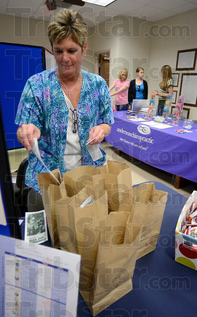 Tribune-Star/Joseph C. Garza<br /> Grab some great information: Pam Jackson, an R.N. with Health Connection, prepares grab bags for patrons of Wednesday's Vigo County employee health fair at the county annex.