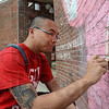 Tribune-Star/Joseph C. Garza<br /> Art from the heart: Rose-Hulman Institute of Technology senior Hobey Tam of Fishers works on the mural he created as a memorial for the late Rose-Hulman president, Matt Branam, Wednesday on the Rose-Hulman campus.