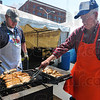 Tribune-Star/Jim Avelis<br /> Hot off the grill: Paul Ingle and Everett Huffman pick brats off the grill at the Strassenfest cook tent early Thursday afternoon. The springtime festival runs from 11:00a.m. until midnight today and from 4:00p.m. until midnight tomorrow.
