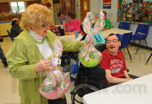 Tribune-Star/Jim Avelis<br /> Down the bunny trail: Alice Stalpeton carries Easter baskets to Ron Handley at the Happiness Bag. Stapleton and her family are carrying on a tradition started by her husband Ed when he would host an Easter Egg hunt at Collett Park each year.