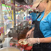 Tribune-Star/Jim Avelis<br /> Fair fare: Susha Muller dips Samoas Girl Scout cookies in batter before deep frying them at the Indiana State Fair Friday afternoon. Her food stand is just east of the Ferris wheel on the midway.