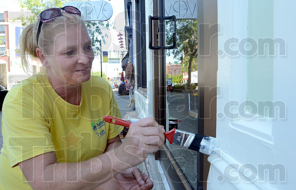 Tribune-Star/Jim Avelis<br /> Touch up work: Brandy Hodge does some touch up painting to the front of Lynn's Boutique Thursday afternoon. She was helping her friend Lynn Henry get the business ready for Saturday's Downtown Block Party.