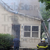 Tribune-Star/Jim Avelis<br /> Heavy damage: Smoke pours from a house at 306 South 16th street Thursday evening. Firefighters cut a vent hole in the roof of the structure to aid in fighting the blaze.