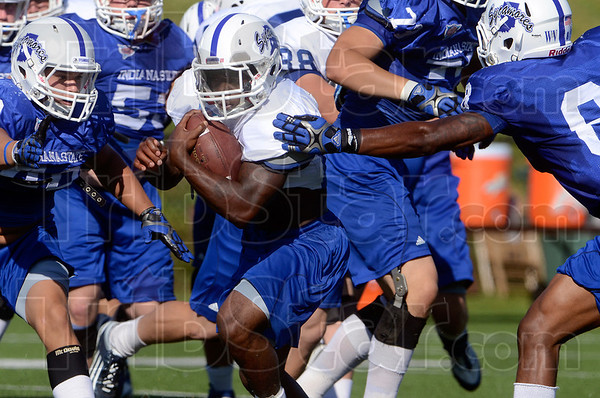 Tribune-Star/Joseph C. Garza<br /> You might get a hand on him, if that: Indiana State running back Shakir Bell runs through the defensive line as teammate Tarris Batiste, right, gets hand on him during team practice Tuesday at Memorial Stadium.