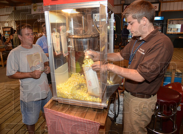 Tribune-Star/Jim Avelis<br /> Learning to lead: Cameron Frazier, right, works the popcorn booth in the Future Farmers of America building at the Indiana State Fair Friday afternoon. Frazier hopes to teach in an agriculture related area in the future.