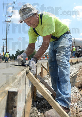 Tribune-Star/Jim Avelis<br /> Finishing touches: Concrete finisher Alan Graffis smooths newly poured cement at the entryway to Southland Shopping Center from Margaret Avenue.