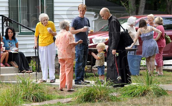 Holy Rosary: Parishoners gather on the sidewalk of the Holy Rosary Catholic Church parish house after Mass Sunday morning.