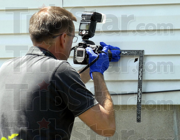 Crime scene: Indiana State Police crime scene investigator Chris Lewis of the Bloomington Post photograph a bullet hole in a house near the scene of Friday's standoff in Linton.