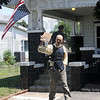 Distress call: The American Flag hangs upside down indicating a distress call at a residence on south east Third Street in Linton. State Police investigator Sgt. Rob Prist communicates with a nearby officer after the conclusion of the incident.