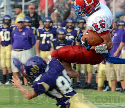 Tribune-Star/Jim Avelis<br /> High flyer: Linton wide reciever Zane Hayden(26) is tackled by Sullivan's Cameron McNeely in first quarter action on the Golden Arrow's field.
