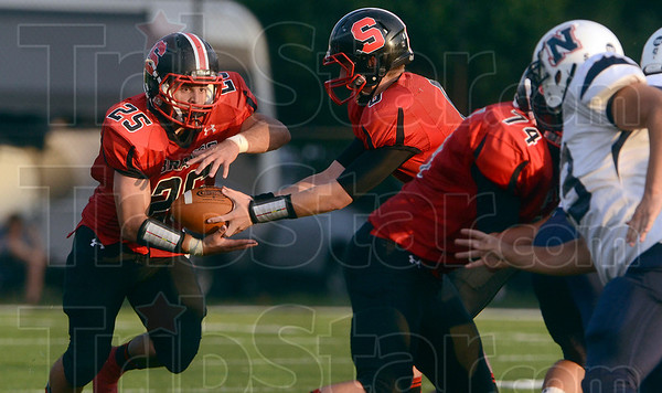 Tribune-Star/Joseph C. Garza<br /> Terre Haute South's Pedro Piloni takes the hand-off from quarterback Danny Etling during the Braves' game against North Friday at Memorial Stadium.