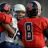 Tribune-Star/Joseph C. Garza<br /> Terre Haute North's Calvin Blank, center, tries to get a hold of South quarterback Danny Etling as he contends with Brandon Russell-Cherry (54) during the Patriots' win Friday at Memorial Stadium.